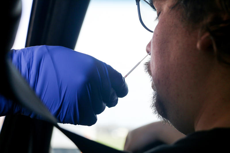 A healthcare worker speaks with someone in a coronavirus drive thru testing facility in Bloomington.
